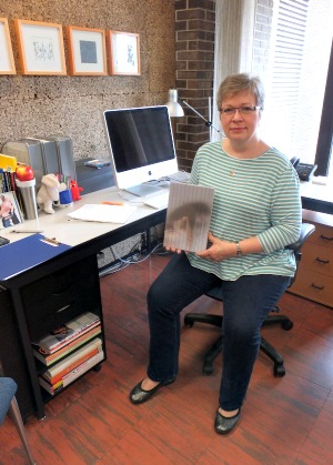 Sue Colberg in her creative studio with the award-winning book The Body in Question(s).